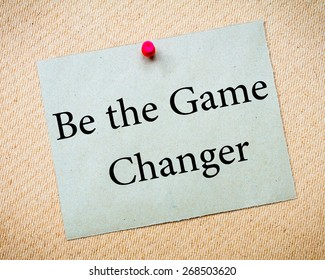 BE THE GAME CHANGER Message. Recycled paper note pinned on cork board. Concept Image
