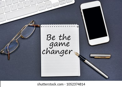 Be the game changer. Text on notebook on a black background