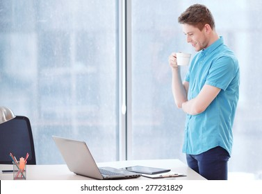 To be glad of results. Smiling businessman standing next to desk covered with office equipment with crossed arms and holding cup of .