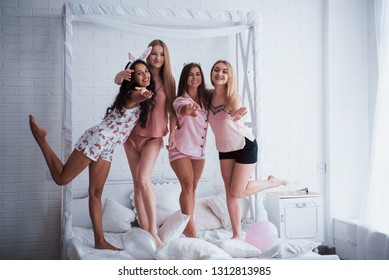 Be happy like these friends. Standing on the luxury white bad at holiday time with balloons and bunny ears. Four beautiful girls in night wear have party.