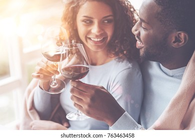 Be happy. Young loving couple sitting close to each other smiling and clinking glasses with wine