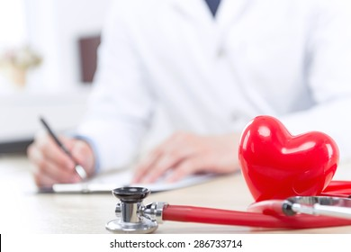 Be healthy. Close up of the heart and stethoscope with cardiologist filling papers on background.