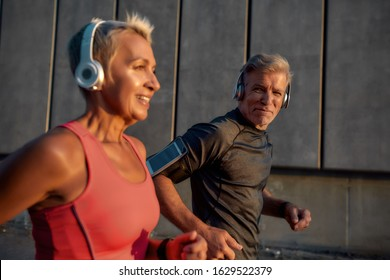 Be healthy. Sporty and happy middle-aged couple in headphones running together through the city street in the morning. Fitness couple. Healthy lifestyle concept