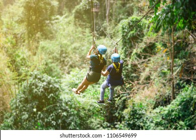 Be hide people go to Zip line in forest with sunlight,Adventure concept