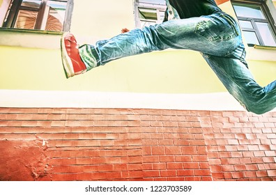 Be late, hurry up, competition or fast running with the leaps for shopping concept. Male fashionable teenager making stride in leap in air. Apparel: blue jeans, red sneakers, black shirt. Copy space.