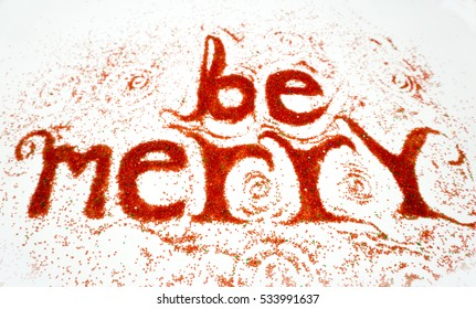 Be merry is a handmade positive message. Text made with red colored sugar on a white board.