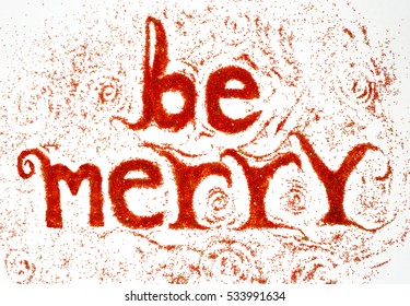 Be merry message with handmade type. Handmade letter made with red colored sugar on white background.