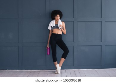 Be motivated! Beautiful sexy fitness woman posing full length with white towel and water bottle wearing sportswear and leaning the grey wall.