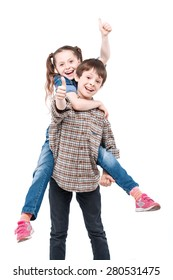 Be my horse. Small handsome boy holding his small pretty sister on his back while both are smiling and showing thumbs up isolated on white background