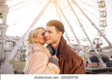 Be my valentine. Happy romantic girlfriend and boyfriend are bonding to each other and kissing while standing on square. They are feeling passion and love. Ferris wheel on background