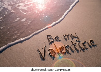 Be My Valentine message handwritten on smooth sand beach with lens flare above oncoming wave