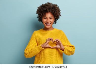 Be my valnetine. Charming young girlfriend confesses in love, shows heart gesture, smiles broadly, has romantic feelings, seeks lonely hearts, feels passion, dressed in casual bright yellow sweater