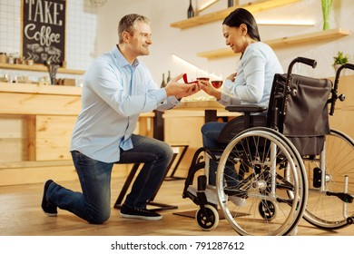 Be my wife. Attractive content well-built man smiling and proposing to his beloved dark-haired handicapped woman and holding a ring while having romantic dinner