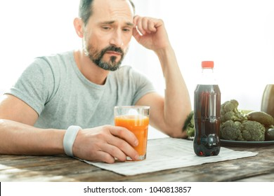 To be or not to be. Disturbed upset handsome man sitting in the bright room by the table holding hand near head and looking at a glass of juice.