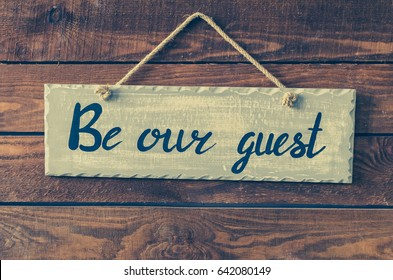 Be our guest - wording on board hanging on a rustic wooden background. Welcome concept. Toned image.