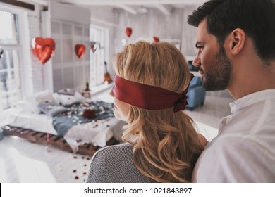 Be patient. Rear view of young woman standing blindfold with her boyfriend while spending time at home