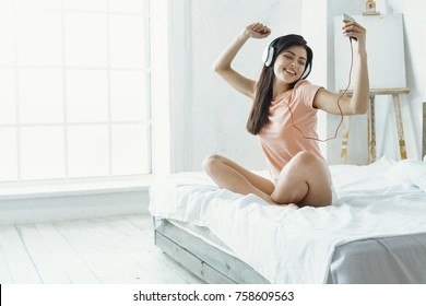 Be positive. Cheerful female expressing positivity and raising both arms while keeping eyes closed