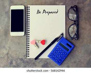 Be Prepared - text on notebook. smartphone,calculator, pen, glasses on the desk. top view.