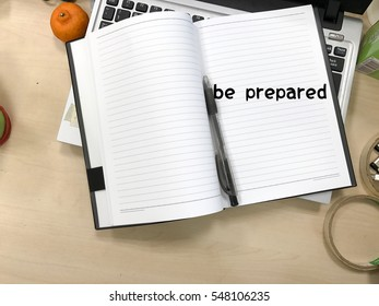 BE PREPARED wrote in the book with the wooden background and messy table concept.