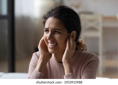 Be quiet. Annoyed nervous latina woman suffer of loud noise at home stick fingers in ears with grimace on face. Stressed young hispanic lady get tinnitus listen to rumbling music from neighboring flat