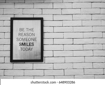 """Be the reason someone smiles today"" qoute in frame hang on the brick wall, black&white theme."