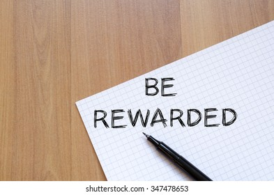 Be rewarded text concept write on notebook with pen