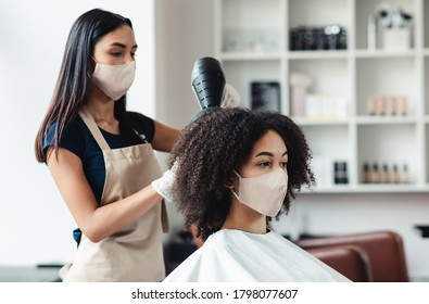 Be safe and beautiful. Hairdresser and customer wearing protective masks at beauty salon, close up