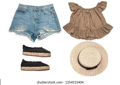 Be in trend. Set of fashion clothes on a white background. Denim shorts, blouse, hat and summer shoes. Top view