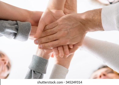 Be united. Low angle of hands of people holding them one on another during psychological group  therapy session