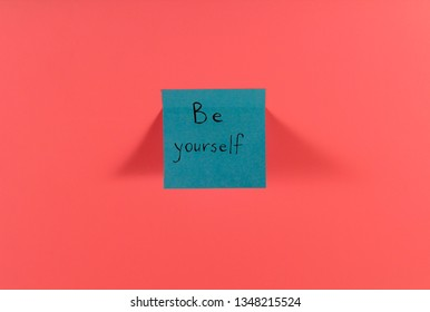 Be yourself. Blue sticky note with inspirational quote on neon pink background. Handwritten positive reminder/advice. Concept for confidence, courage and motivation. Sign of moral support.