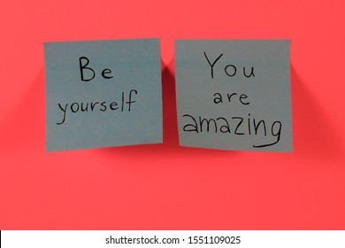 Be yourself. You are amazing. Two blue sticky notes with inspirational quotes on neon pink background. Handwritten positive reminder/advice. Sign of moral support.