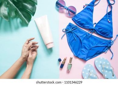Beach accessories, Bikini, sunglasses, sandals with woman's hands and beauty products on pastel color background, Summer beauty concept