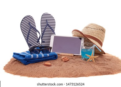 Beach accessories, glass of cool cocktail and computer tablet, lying on the sand on white background. Concept of sea vacation and travel. Summer background, Travel agency. Internet shop