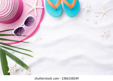 Beach accessories Green tropical leaves with sunglasses, flip flop starfish, beach hat and sea shell on white sand beach background for summer holiday and vacation concept.