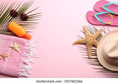 Beach accessories on pink background, flat lay. Space for text