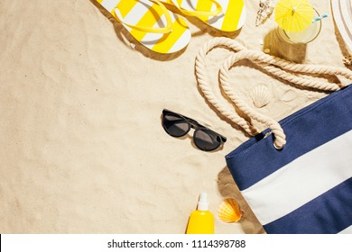 Beach accessories on the sand. Bag, flip flops and hat and sunscreen. Summer vacation.