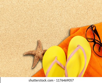 Beach accessories on sand. Flip flops and sunglasses
