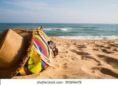 Beach accessories on the sandy shore of the sea. Concept of summer vacations.