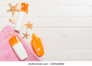 beach accessories on a white wooden background top view. Sunscreen, towel and seastar. Travel healthcare accessories top view.