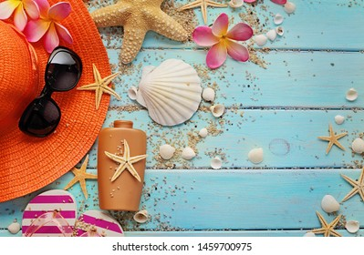 beach accessories on wooden board, summer hat, flip flop shoes, sunglasses, and suntan lotion. seashells