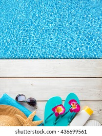 Beach accessories on wooden desk placed over swimming pool. Copyspace for text