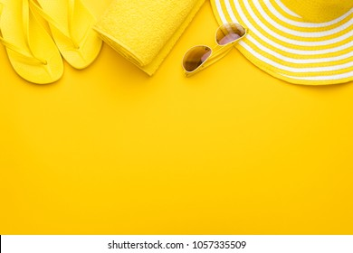beach accessories on the yellow background - sunglasses, towel. flip-flops and striped hat. summer is coming concept