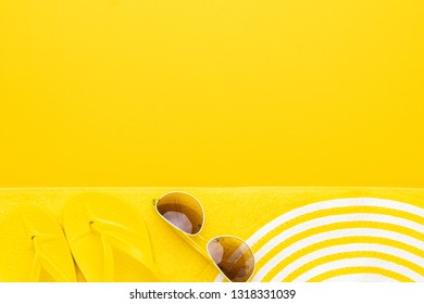 beach accessories on the yellow background - sunglasses, towel. flip-flops and striped hat. summer is coming concept with copy space
