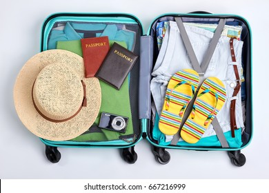 Beach accessories in opened suitcase. Travelling wheeled bag, different clothes.