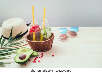 Beach accessories, palm leaf and avocado nex to a couple of glass bottles of refreshing drinks on the wooden table.