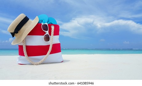 Beach accessories picnic bag hat sunglasses and flip flops on white sandy beach