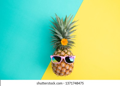 Beach accessories pineapple with pink sunglasses on green and yellow pastel background for summer holiday and vacation concept.