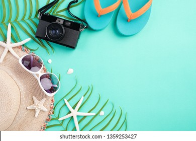 Beach accessories retro film camera, sunglasses, flip flop, starfish beach hat and sea shell on bright pastel green background for summer holiday and vacation concept.