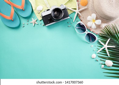 Beach accessories retro film camera, sunglasses, flip flop starfish beach hat and sea shell on green pastel background for summer holiday and vacation concept.