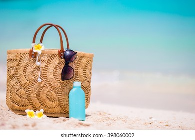 Beach accessories - straw bag, headphones, bottle of cream and sunglasses on the beach